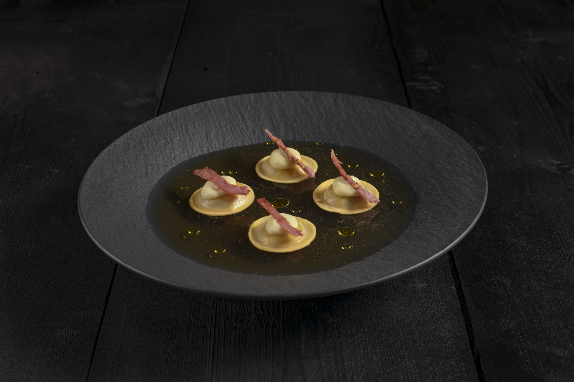 Gruyère ravioli in artichoke broth with toasted speck.